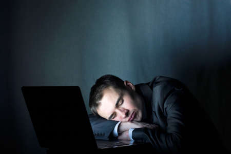 working late: tired businessman sleeping at the computer