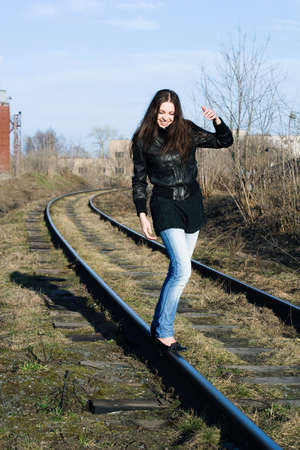 portrait of a beautiful laughing female model on a railway track