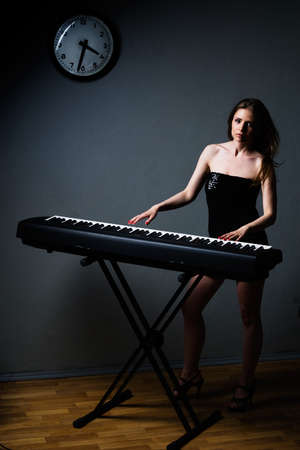 expression girl in black dress playing on keyboard