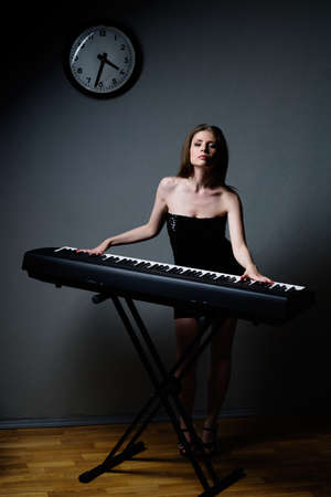 expression girl in black dress playing on keyboard photo