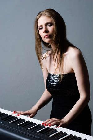 beautiful girl in black dress playing on keyboard photo