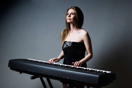 beautiful girl in black dress playing on keyboard photo