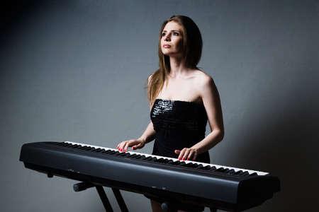 beautiful girl in black dress playing on keyboard Stock Photo