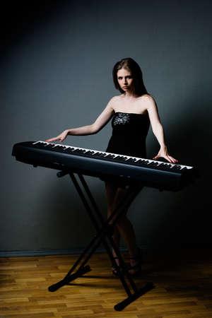 beautiful girl in black dress playing on keyboard Stock Photo - 8632447