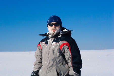 bearded man in sunglasses with snow on the face