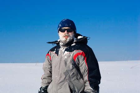hombre con barba: hombre con barba, gafas de sol con la nieve en la cara Foto de archivo