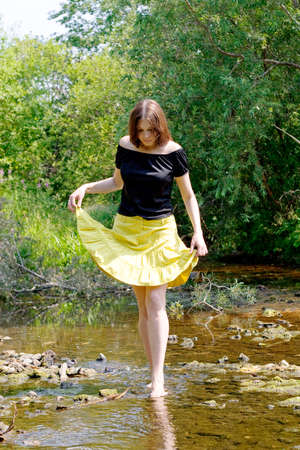 young woman crossing little stream in forest