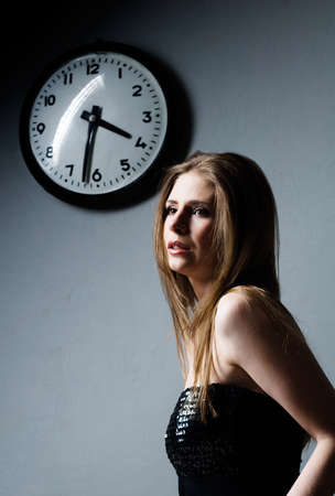 attractive young woman and clock on gray background Stock Photo - 8632446