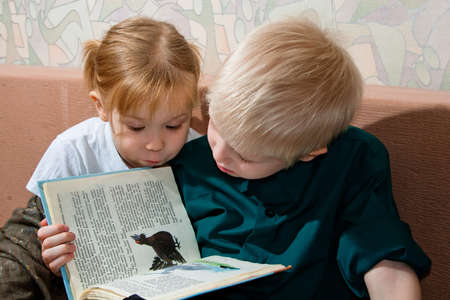 brother and sister read a book together
