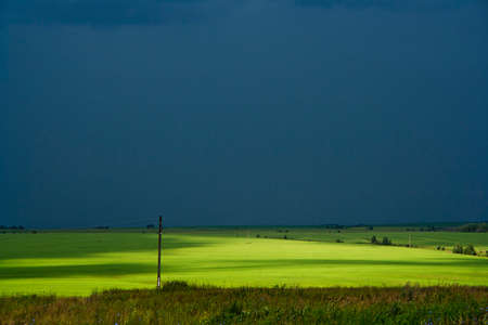 Sunlight breaks through the storm clouds on the green field Stock Photo