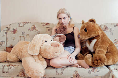 Woman sitting on couch with her plush toys Stock Photo