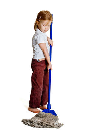 A little girl with a long mop washes the floor photo