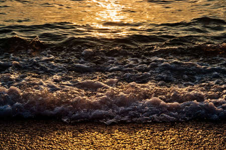 ebb: closeup of yellow sea wawes at sunset Stock Photo