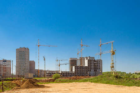 Houses under construction and cranes on the construction site