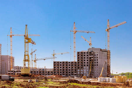 Houses under construction and cranes on the construction site photo