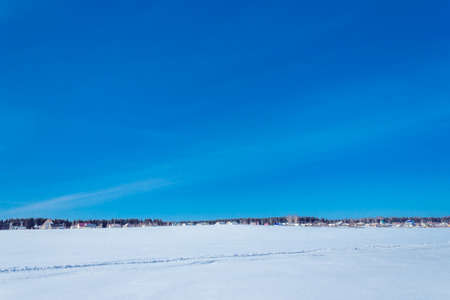 Clear blue sky over a wide snow-covered field