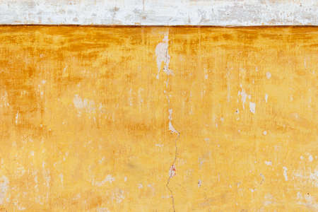 Old cracked yellow-white stucco wall. Texture