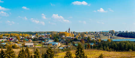 Panorama of Russian village Sredneivkino with a church in the autumn