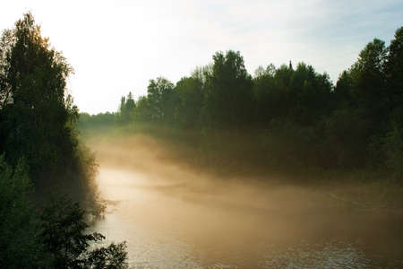 Fog over the forest river at sunset