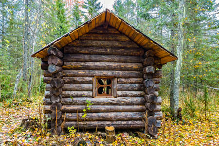 Little old Russian log hut in a forest in autumn Stock Photo