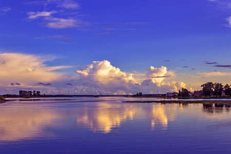 Evening sky with beautiful clouds reflected in the calm water of the river