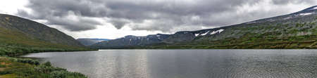 Lake and mountain range in the Subpolar Urals on a rainy summer day