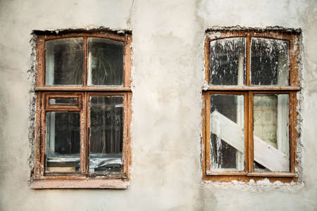 stucco house: Background of old white stucco wall with two wooden windows with paint stains after renovation, parts of architecture, retro house reparation, close-up Stock Photo