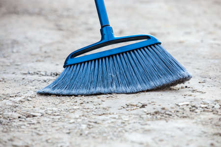 scrubbing up: Close up of blue broom brushing grey crumbled concrete sidewalk outdoors, cleaning
