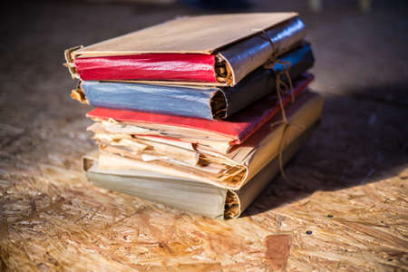 Pile of old documents in colorful cardboard folders in warm sunlight