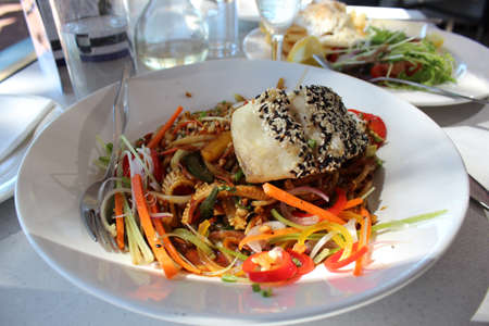 barramundi: Grilled Barramundi fish fillet  in black and white sesame seeds with Asian stir fried vegetables and hokkein noodles
