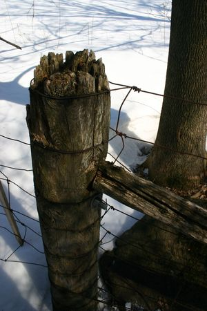 fencepost: A shadowed fencepost against a background of deep snow. Stock Photo