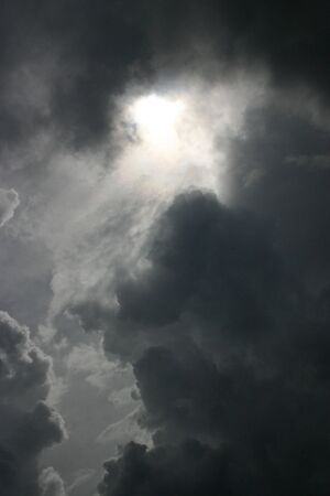 The sun tries vainly to shine through dark, gray angry storm clouds. Banco de Imagens