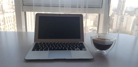 Still-life portrait of grey computer with black buttons, coffee mug on table. 免版税图像