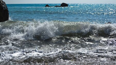 sea foam of a sea wave rolling ashore on a clear sunny day 스톡 콘텐츠