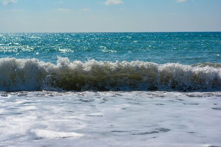Seascape on a clear sunny day at sea with waves crashing onto a pebble-sand beach, creating sea splashes, bubbles and foam