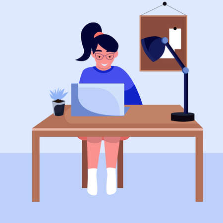 Young girl with glasses sitting at her Desk and looking at the computer, office at home