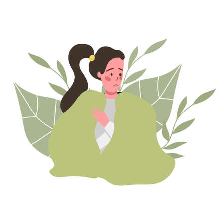the girl is sitting wrapped in a warm blanket, feeling unwell, ill. girl on the background of abstract leaves