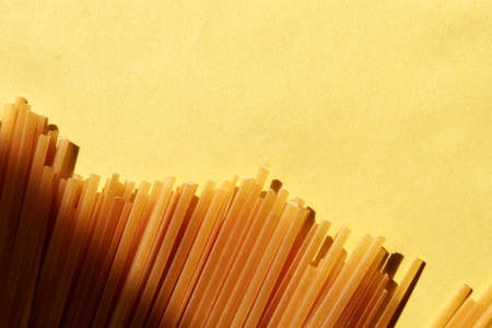 Scattered spaghetti on a bright yellow background