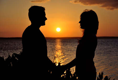 happiness people silhouette on the sunset: Happy couple holding hands at sunset Stock Photo