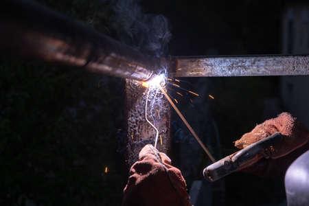 Industrial Worker at the factory welding closeup. Welder working welding steel