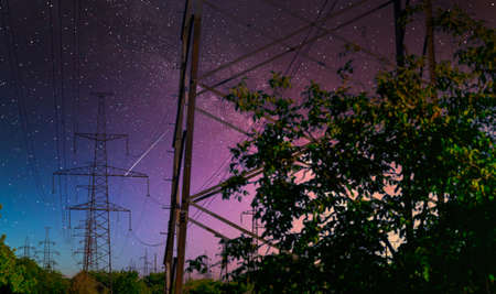 high voltage pole with Milky way on sky. industrial view of high voltage lines.