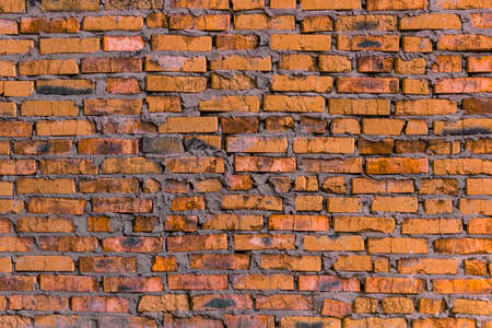 quantities: brickwork of the cracked and weathered stained rough brick. Art edition. Orange (yellow) brick.