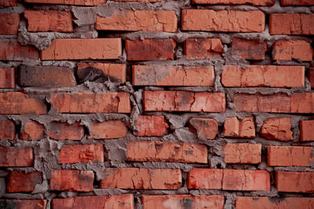 sidewall: brickwork of the cracked and weathered stained rough brick. Art edition. Rustic red stylized brick. Stock Photo