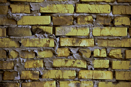 sidewall: brickwork of the cracked and weathered stained rough brick. Art edition. Rustic yellow-green stylized brick. Stock Photo