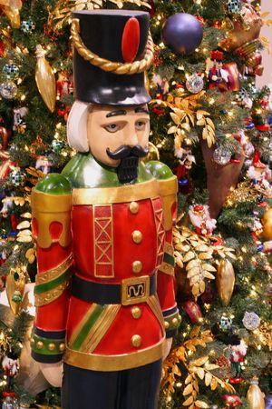 Nutcracker ornament next to Christmas tree photo