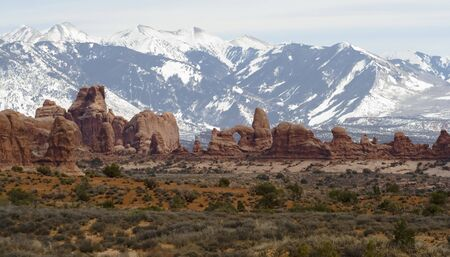 Arches landscape with snow-capped mountain backdrop Imagens