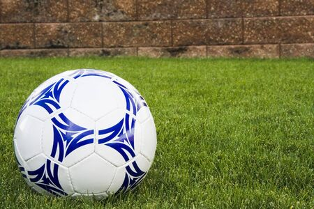 White and blue soccer ball and brick wall