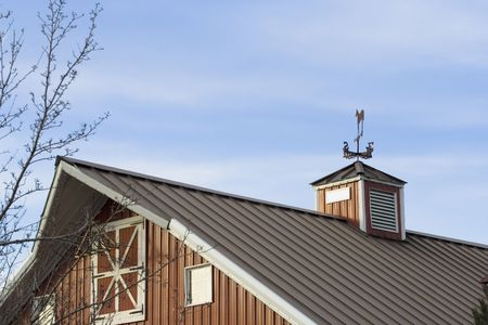 bard: Red barn roof made out of metal with weather vane on top Stock Photo