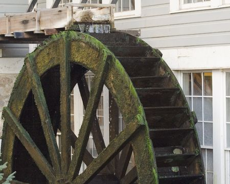 Old pioneer era wood waterwheel attached to building for grinding grain