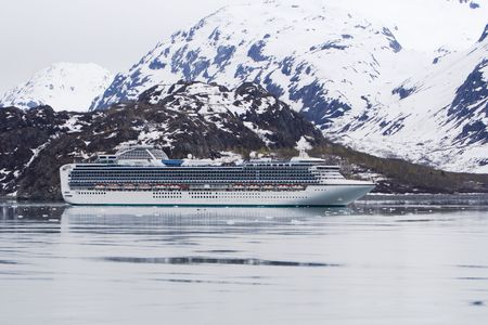 Cruise ship surrounded by beautiful snowcapped mountains and water in Glacier Bay National Park Alaska Фото со стока